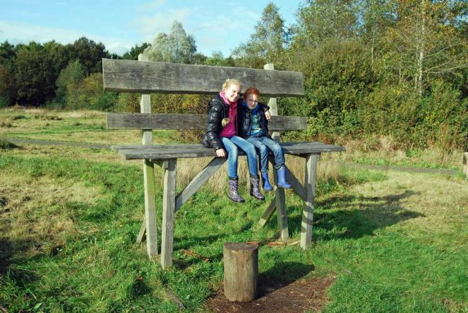 Kinderen op zeer grote houten bank fotograaf Jaap Roos